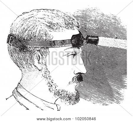 Man with electric light attached to strap on forehead, vintage engraved illustration. Usual Medicine Dictionary - Paul Labarthe - 1885.