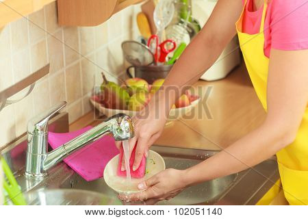 Woman Doing The Washing Up In Kitchen