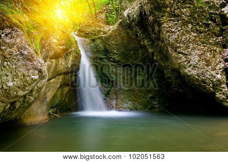 Nice landscape with waterfall on sunset background