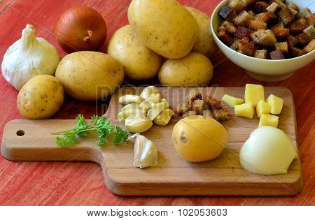 Ingredients for garlic soup on chopping board - potatoes, onion, garlic, roasted bread and parsley