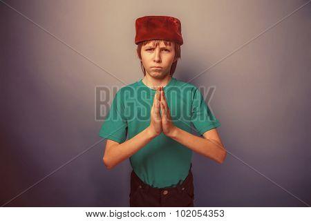 Muslim boy of ten  years, skullcap, prayer on a gray background