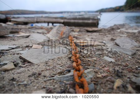 rusty chain holding abandoned docks at lake
