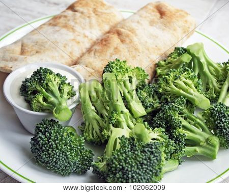Two filled Tortilla wraps with a side of fresh raw broccoli and a container of creamy dressing for d