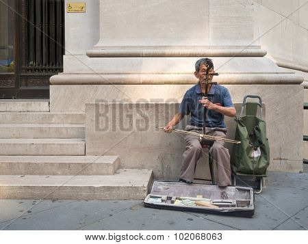 NEW YORK,USA - AUGUST 16,2015 : Asian immigrant playing an instrument for money next to Wall Street in New York City
