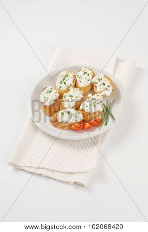 crunchy croutons with chives spread on white plate and place mat