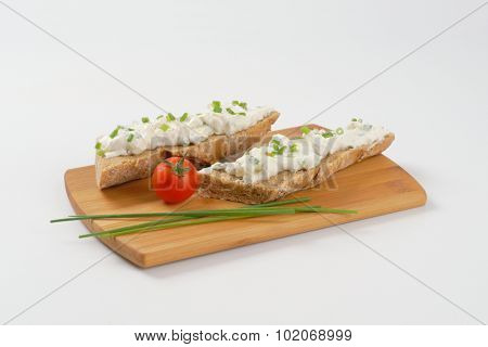 open faced sandwich with chives spread on wooden cutting board