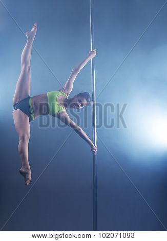 Pole dance. Strong girl froze in stretching pose