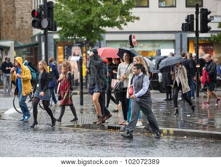 Group of people with umbrellas crossing the road
