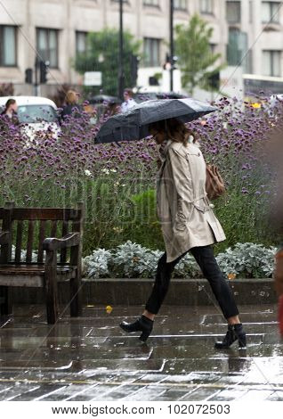 Woman with umbrella  walking in rain. City of London