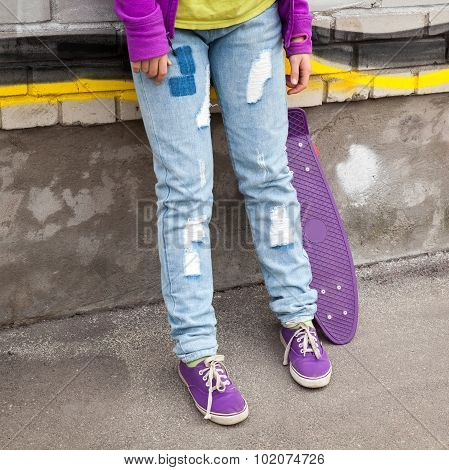 Teenager In Jeans And Gumshoes With Skateboard