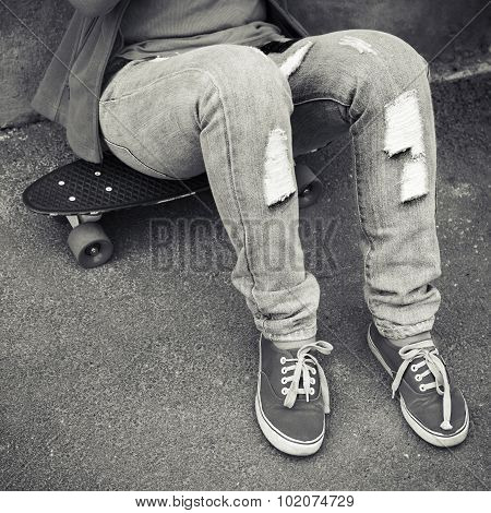 Teenager In Jeans And Gumshoes Sits On Skateboard