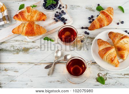 Fresh Croissants And Cups Of Tea With Berries For Breakfast.