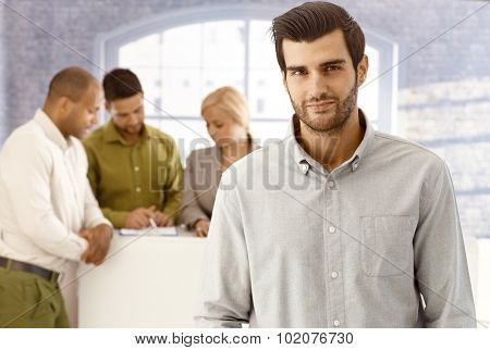 Closeup portrait of handsome young businessman looking at camera.