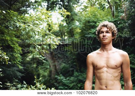 Close-up Portrait Of Attractive Young Man On Forest Background With Copy Space