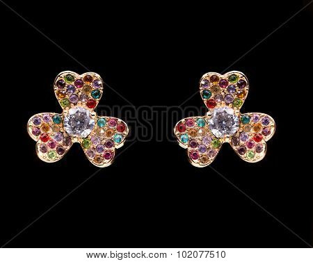 gold earrings with white little stones. in the form of flowers