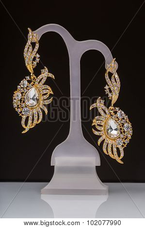 gold earrings with white little stones