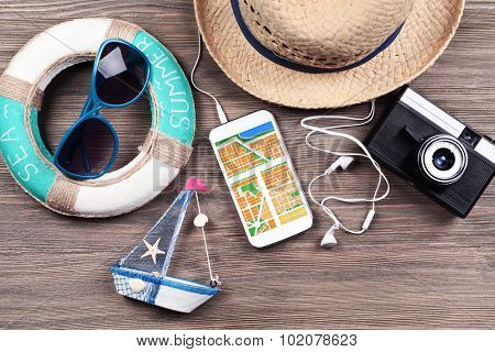 Smart phone with map gps navigation application and travel accessories on table, close-up