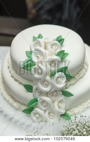 A Multi Level White Wedding Cake On A Silver Base And Flowers On Top