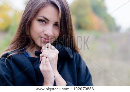 Charming girl in coat gently smiling on autumn outdoor background.
