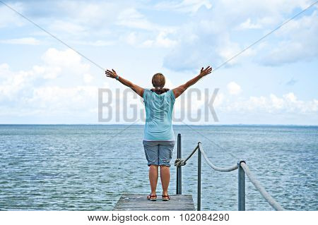 Woman With Arms Up In Front Of Blue Sea