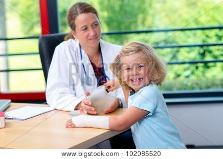 Female Pediatrician Bandaging The Arm Of A Little Girl