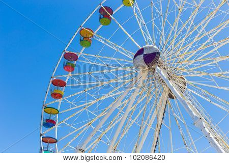 Giant Ferris Wheel In Amusement Park With Blue Sky Background