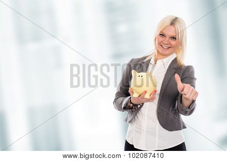 Smiling Young Business Woman With Piggy Bank And Thumb Up