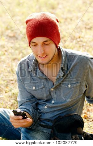 Young Men Sited On The Grass Looking For Cell Phone