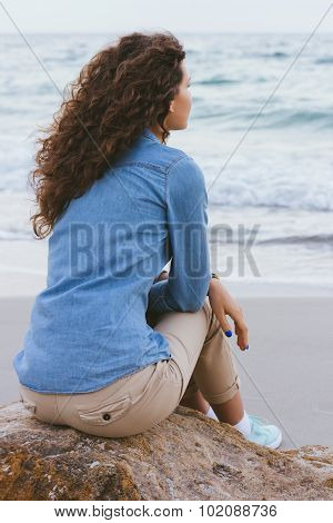Beautiful Slim Woman With Curly Hair Sitting On A Rock By The Sea