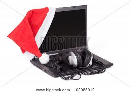 Red Santa Hat On The Notebook Computer With Headphones