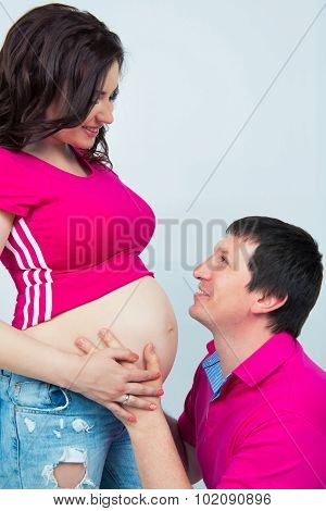 Happy Pregnant Family. Future Dad Hugs Tummy And Tenderly Looks At His Wife