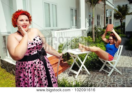 Plus size curly red hair smiling woman watering hose  plant and her sister is reading book