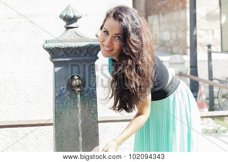 portrait of pretty girl drinks water from source in summer city