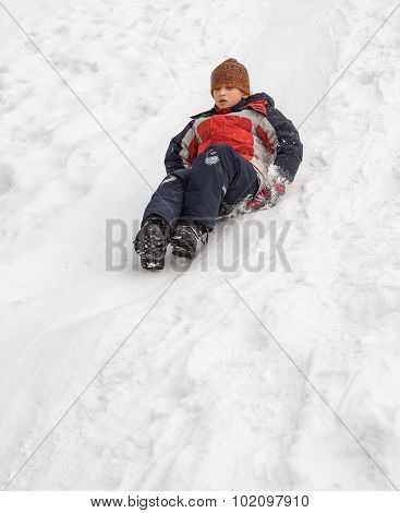 Winter fun - sledding at winter time. Young boy enjoying a sledge ride in a snowy winter park.