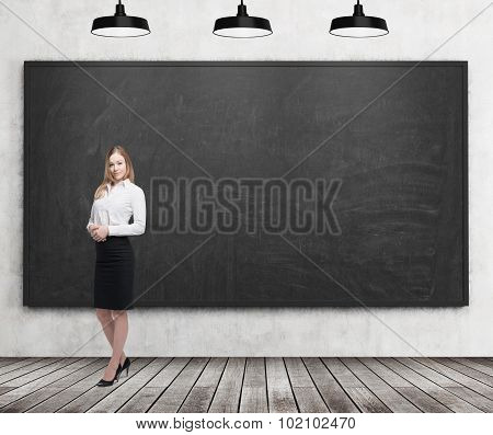 Full Length Beautiful Lady In Formal Clothes. White Shirt And Black Skirt. Black Chalkboard On The W