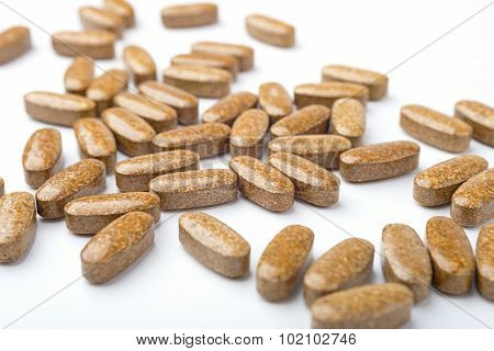 A Heap Of Brown Medicine Pills On White Surface.