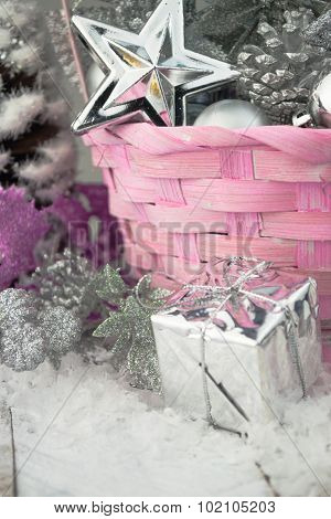 Pink Christmas basket with silver toys on a white wooden background