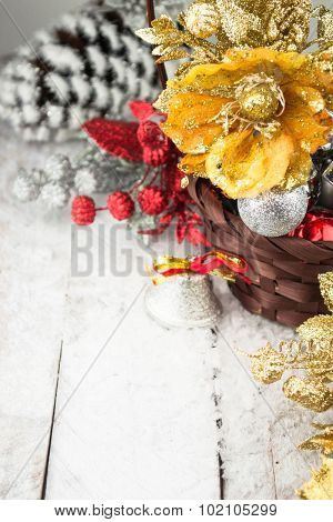 Brown Christmas basket with silver and gold toys on a white wooden background