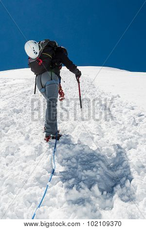 Female climber ascending a snowy slope.