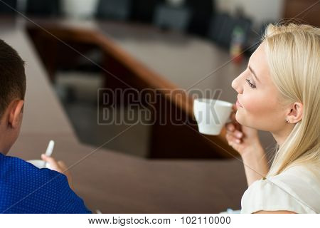 Young Beautiful Cheerful Business Woman With A Cup Of Coffee Looking At Partner