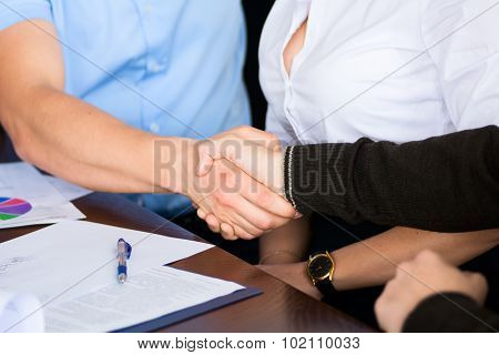 Handshake Of Two Businessmen On The Background Of The Secretary Of The Woman After Signing The Contr