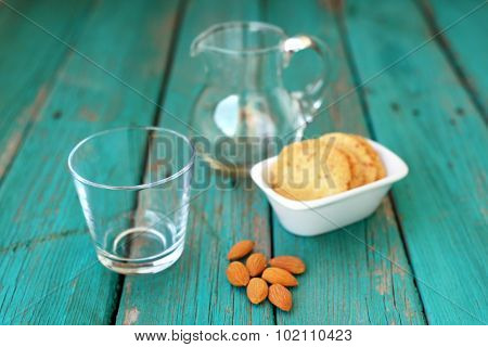 Empty Glass  With Homemade Almond Cookies And Whole Almonds On Shabby Turquoise Wooden Table
