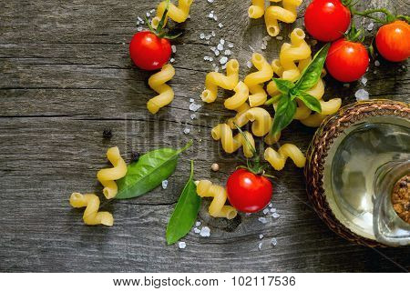 Pasta, Fresh Cherry Tomatoes And Sunflower Oil On A Dark Gray Background