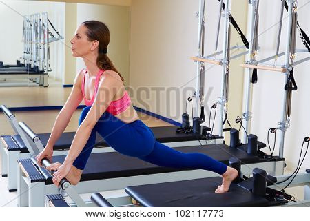 Pilates reformer woman front split exercise workout at gym indoor