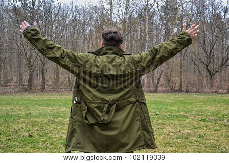A young man in a coat with outspread arms in forest