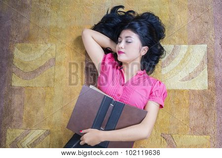 Female Student Holds Book And Sleeping On Carpet