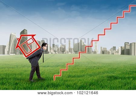 Man Carrying House Icon At Field