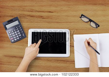 Student Hand Using Tablet While Writing On Book