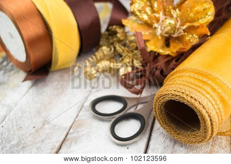Golden wrapping paper and bow for Christmas present decoration on wood