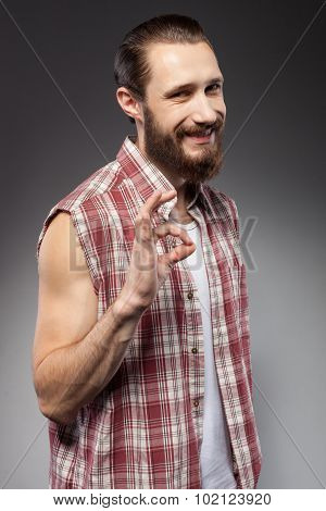 Handsome young man with beard is gesturing positively